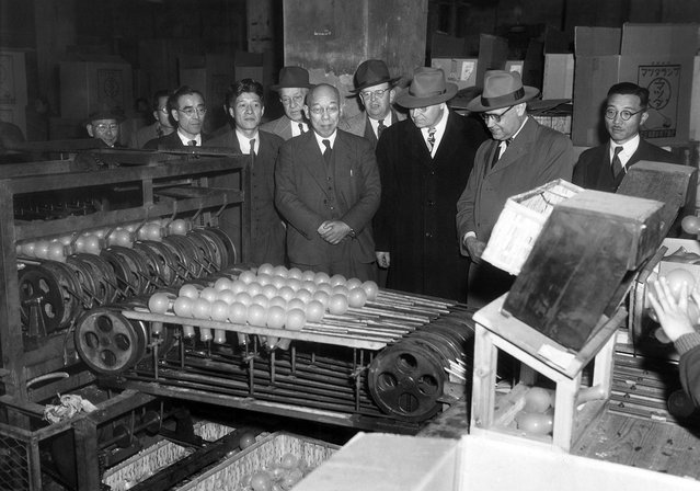 Industrial training experts watch a light bulb machine drop bulbs down to other workers who sort them according to defects at Tokyo Shibaura Electric Co. in Tokyo on January 25, 1951. (Photo by Arthur Curlis/AP Photo/U.S. Army via The Atlantic)