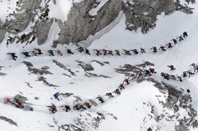 """A group of skier climbs the 'Col du Pacheu' during the 69th edition of the """"Trophees du Muveran"""", a Ski Mountaineering race throught the Swiss Alps, above Les Plans-sur-Bex, Switzerland, 03 April 2016. (Photo by Laurent Gillieron/EPA)"""