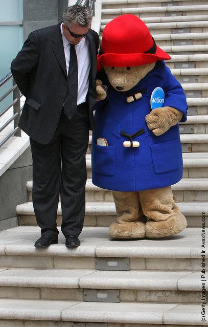 Paddington Bear's guide helps him walk down stairs