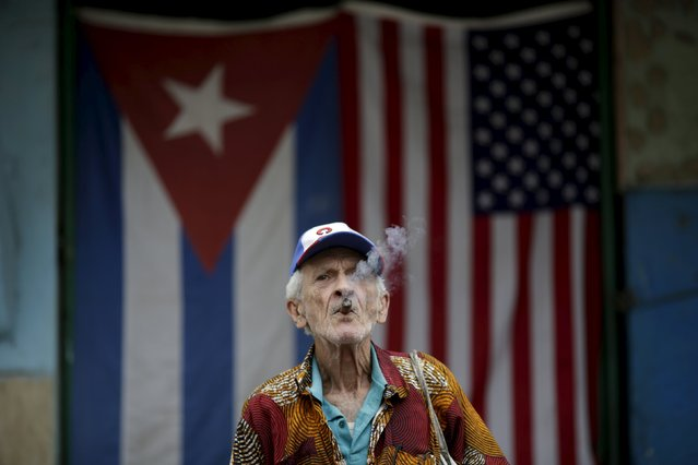 "Pascual Montero, 86, who collects plastic containers from restaurants and resells them, smokes a cigar while posing in front of the Cuban and U.S. flags in Havana, March 25, 2016. Regarding Obama's historic visit to the island, Montero said, ""It was perfect and I have hopes that some day a lot of problems can be resolved"". (Photo by Ueslei Marcelino/Reuters)"