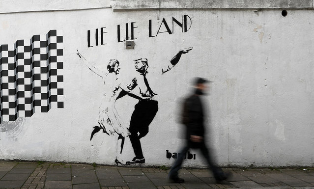 A pedestrian passes a new piece of art by street artist Bambi in London. in London, February 16, 2017. The work, entitled Lie Lie Land, features a dancing British Prime Minister Theresa May and President Donald Trump in the pose made famous by the movie La La Land. (Photo by Kirsty Wigglesworth/AP Photo)