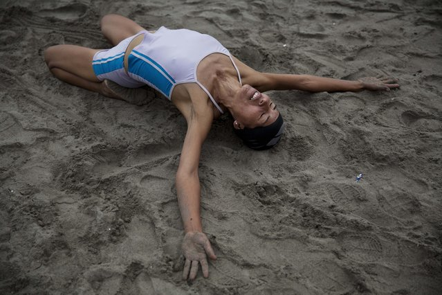 In this May 15, 2015 photo, Juana Coripuna stretches and meditates on Fishermen's Beach in Lima, Peru. Juana, 44, said she started going to the beach six years ago, and that thanks to meditation and swimming, she's improved both physically and mentally. (Photo by Rodrigo Abd/AP Photo)