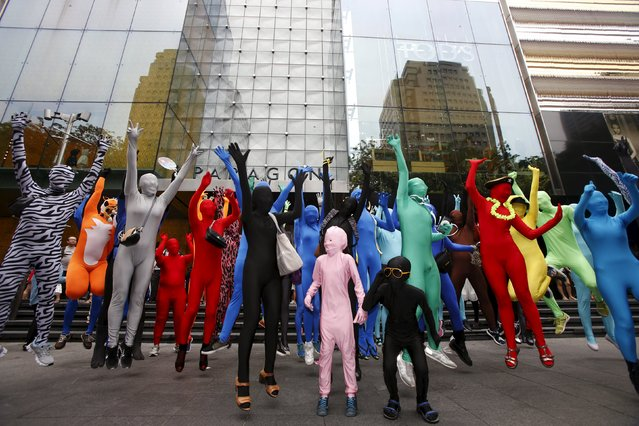 Participants wearing Zentai costumes, or skin-tight bodysuits from head to toe, pose for photos during a march down the shopping district of Orchard Road during Zentai Art Festival in Singapore May 23, 2015. (Photo by Edgar Su/Reuters)
