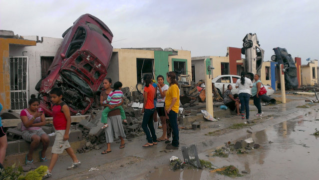 Residents stand outside their homes as damaged cars are seen after a tornado hit the town of Ciudad Acuna, state of Coahuila, May 25, 2015. At least 10 people died on Monday morning after a tornado hit Ciudad Acuna, a Mexican city on the border with Texas, Mayor Evaristo Lenin Perez said. (Photo by Ramiro Gomez/Reuters)