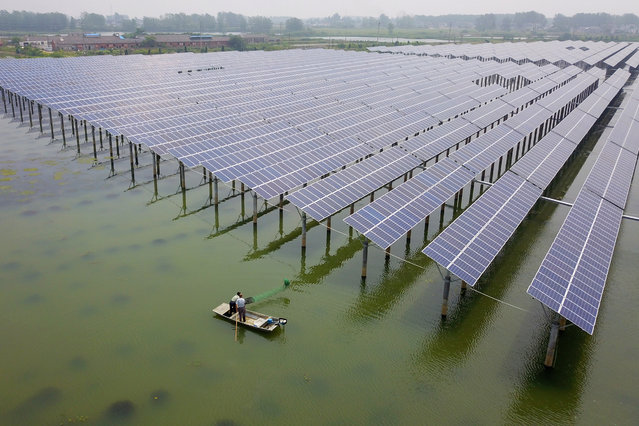 Aerial view of fishermen catching crayfish next to photovoltaic solar pannels at a fishery-solar hybrid photovoltaic power station on June 24, 2019 in Yangzhou, Jiangsu Province of China. China's electricity consumption, a key barometer of economic activity, rose 2.3 percent year-on-year to 566.5 billion kilowatt hours in May, according to the National Energy Administration. (Photo by Meng Delong/VCG via Getty Images)