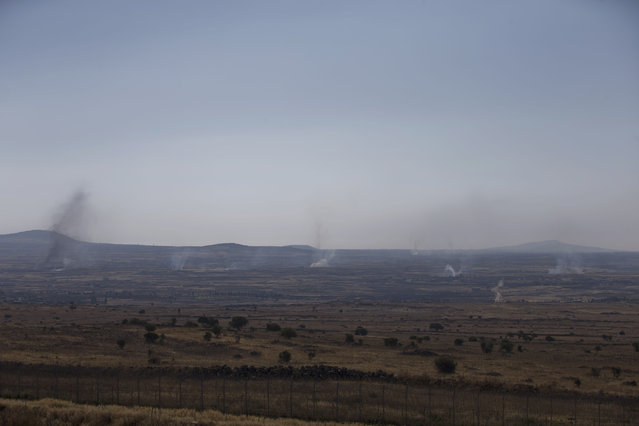 Smoke and explosions from the fighting between forces loyal to Syrian President Bashar Assad and rebels, in the Quneitra area, seen from the Israeli controlled Golan Heights, Wednesday, June 17, 2015. Syrian rebels attacked government troops positions Wednesday near the Israeli-occupied Golan Heights in what appears to be an attempt by insurgents to capture more areas south of Syria from President Bashar Assads forces, activists said. (AP Photo/Ariel Schalit)