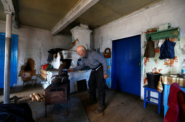 Ivan Shamyanok, 90, is seen in his house in the village of Tulgovichi, near the exclusion zone around the Chernobyl nuclear reactor, Belarus March 15, 2016. Shamyanok lives a quiet life. He gets up at 6 a.m. when the national anthem is played on the radio, lights his cast iron stove to heat his breakfast and feeds his pigs and his dog. (Photo by Vasily Fedosenko/Reuters)