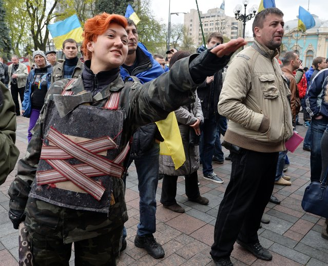 """A Maidan self-defence activist, holding a club and an ax, attends outside the Ukrainian Parliament in Kiev on April 15, 2014, during a rally of protesters who demand authorities to take actions against separatism on the eastern part of the country. Russian Foreign Minister Sergei Lavrov on Tuesday warned Kiev against using force to quell pro-Moscow separatists in eastern Ukraine, saying the """"criminal"""" act would undermine talks planned in Geneva. (Photo by Sergei Supinsky/AFP Photo)"""