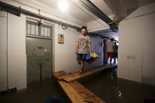 Students walk on a makeshift bridge inside their dormitory building which is partially submerged by floodwater, at an university campus after heavy rainfall hit Nanjing, Jiangsu province, China, June 28, 2015. (Photo by Reuters/Stringer)