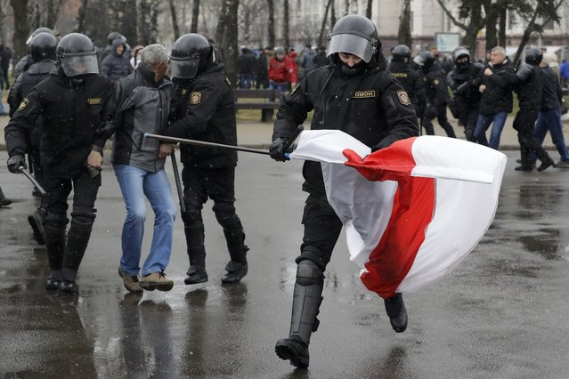 A Belarus policeman runs with an opposition flag as other detain a protester during an opposition rally in Minsk, Belarus, Saturday, March 25, 2017. (Photo by Sergei Grits/AP Photo)