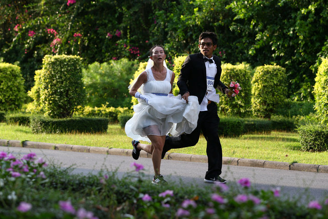 """A couple participates in the """"Running of the Brides"""" race in a park in Bangkok, Thailand March 25, 2017. (Photo by Athit Perawongmetha/Reuters)"""