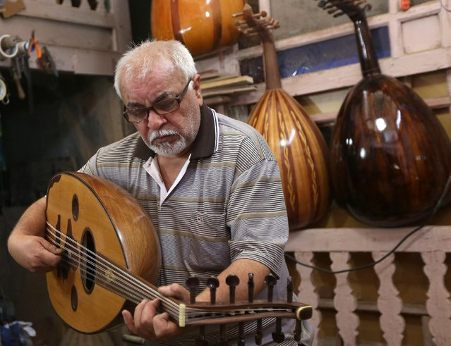 "In this photo taken Saturday, June 20, 2015, Mahmoud Abdulnabi tries out an oud, an Arabic instrument related to the lute, at his workshop in Baghdad, Iraq. ""The oud is different than other musical instruments"", said Abdulnabi, who has crafted ouds played by some of Iraq's best known musicians, many of whom look down from headshots on the walls. ""If you feel joyful, it can play your joy. If the circumstances are sad it can play your sorrow and... help to empty whatever is in your chest"". (Photo by Hadi Mizban/AP Photo)"