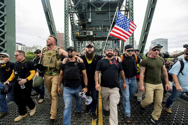 "Members of the Proud Boys and other right-wing demonstrators march across the Hawthorne Bridge during an ""End Domestic Terrorism"" rally in Portland, Ore., on Saturday, August 17, 2019. The group includes organizer Joe Biggs, in green hat, and Proud Boys Chairman Enrique Tarrio, holding megaphone. (Photo by Noah Berger/AP Photo)"