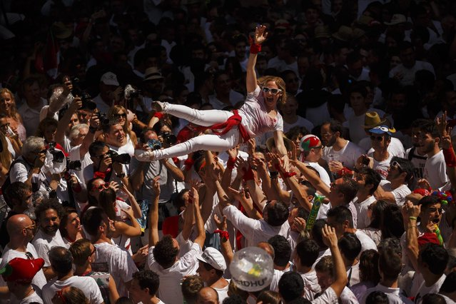"""Revelers celebrate during the launch of the """"Chupinazo"""" rocket, to celebrate the official opening of the 2015 San Fermin fiestas in Pamplona, Spain, Monday, July 6, 2015. (Photo by Daniel Ochoa de Olza/AP Photo)"""