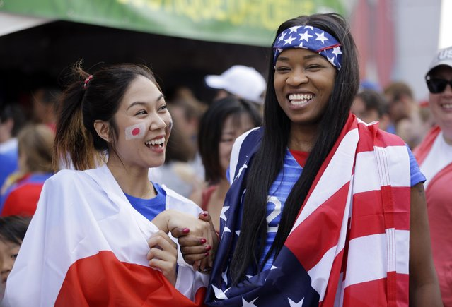 Risa Suzuki, left, of Japan, and Kerrry Haughton, of New York, smile after posing for photographers outside BC Place stadium before the FIFA Women's World Cup soccer championship between the United States and Japan later in the day, in Vancouver, British Columbia, Canada, Sunday, July 5, 2015. (Photo by Elaine Thompson/AP Photo)