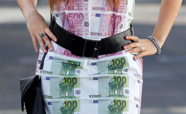 A woman wears a home-made dress featuring imitation 100 and 500 euro notes as she walks in Bordeaux, southwestern France, November 7, 2014. (Photo by Regis Duvignau/Reuters)