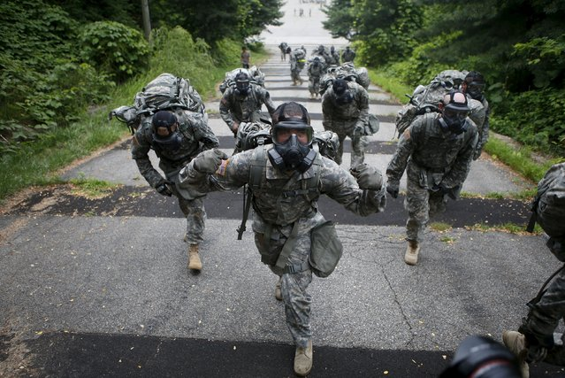A soldier (C) of the U.S. Army 23rd chemical battalion wearing a gas mask poses for photographs as others march during a competition to test individual soldier skills at Camp Stanley in Uijeongbu, South Korea, July 8, 2015. The 23rd chemical battalion left South Korea in 2004 but the battalion with about 250 soldiers returned to South Korea in January 2013 to support South Korean military and the U.S. troops based in the South, according to the infantry division. (Photo by Kim Hong-Ji/Reuters)