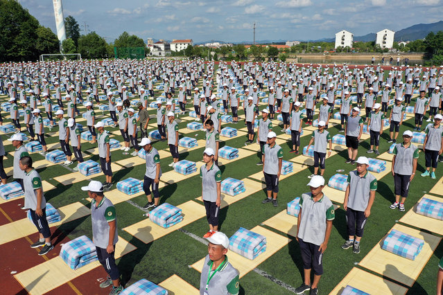 Aerial view of new students participating in a quilt-folding competition on playground during the military training of Dongyang Vocational Education Center School on August 26, 2019 in Dongyang, Zhejiang Province of China. More than 1,400 new students participated in a quilt-folding competition on Monday in Dongyang Vocational Education Center School, Zhejiang. (Photo by Hu Yanghui/VCG via Getty Images)