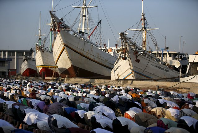 Muslims pray next to traditional Indonesian Phinisi ships on Eid al-Fitr at Sunda Kelapa port in Jakarta, Indonesia July 17, 2015. (Photo by Darren Whiteside/Reuters)