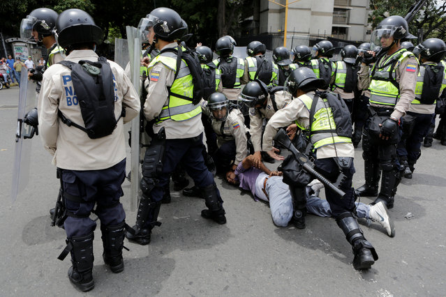 Riot police officers detain a demonstrator during clashes with opposition supporters in a rally to demand a referendum to remove President Nicolas Maduro in Caracas, Venezuela, May 18, 2016. (Photo by Marco Bello/Reuters)