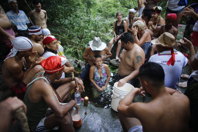 In this photo taken October 12, 2019, Juan Carlos Paso performs a cleansing ritual on a woman in a pool of water on Sorte Mountain where followers of indigenous goddess Maria Lionza gather annually in Venezuela's Yaracuy state. Devotees say the number of followers swells as Venezuelans turn for answers to the struggle of daily life outside traditional political system, churches and hospitals. (Photo by Ariana Cubillos/AP Photo)