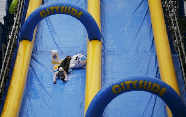 A man enjoys a ride on a 350-meter (1148 feet) long water slide during 2015 City Silde Festa in central Seoul, South Korea, July 19, 2015. (Photo by Kim Hong-Ji/Reuters)