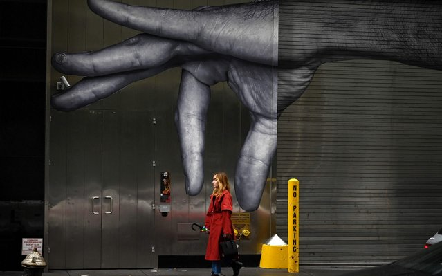 A woman passes a mural in Manhattan on October 27, 2019 in New York City. (Photo by Johannes Eisele/AFP Photo)
