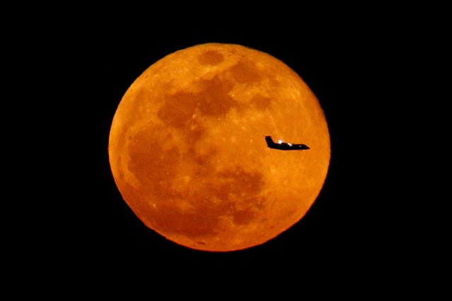 A plane descending into Newark Liberty International Airport crosses over the full moon rising seen from Eagle Rock Reservation, Wednesday, March 23, 2016, in West Orange, N.J. (Photo by Julio Cortez/AP Photo)