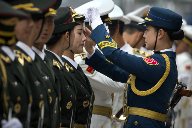 An officer wipes sweat off the face of a Chinese People's Liberation Army (PLA) honor guard soldier as they rehearse for a welcoming ceremony for New Zealand's Governor-General Sir Jerry Mateparae at the Great Hall of the People in Beijing, Tuesday, July 21, 2015. (Photo by Mark Schiefelbein/AP Photo)