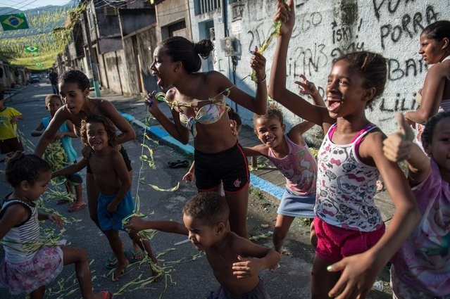 Girls help help to decorate a street for the FIFA World Cup 2014 in Rio de Janeiro, Brazil, on June 11, 2014, on the eve of the opening of the event. (Photo by Yasuyoshi Chiba/AFP Photo)