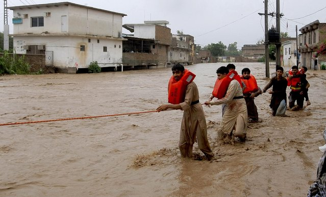 Local residents cross a flooded street near a stream overflowing due to heavy rains in a suburb of Peshawar, Pakistan, Sunday, July 26, 2015. (Photo by Muhammad Sajjad/AP Photo)