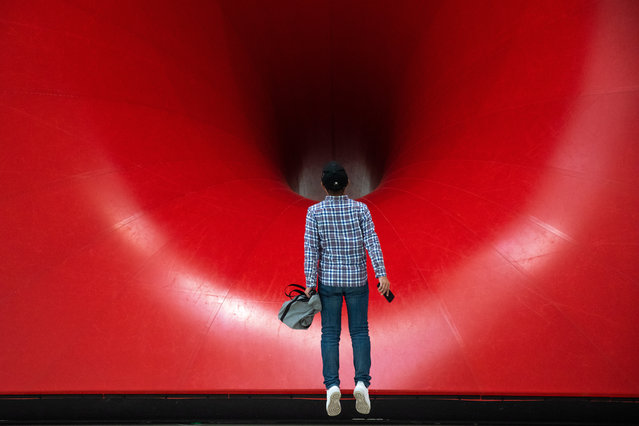 "A visitor jumps to look at ""Sectional Body preparing for Monadic Singularity"" artwork during an exhibition of British-Indian artist Anish Kapoor, at the CAFA Art Museum, in Beijing, China, 19 November 2019. The first solo museum show in China for Anish Kapoor presents his most significant works and runs until 01 January 2020. (Photo by Roman Pilipey/EPA/EFE)"