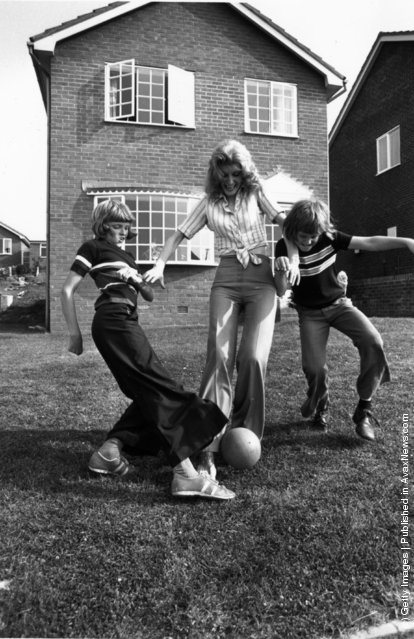1975: English singer and comedienne Marti Caine playing football with her sons