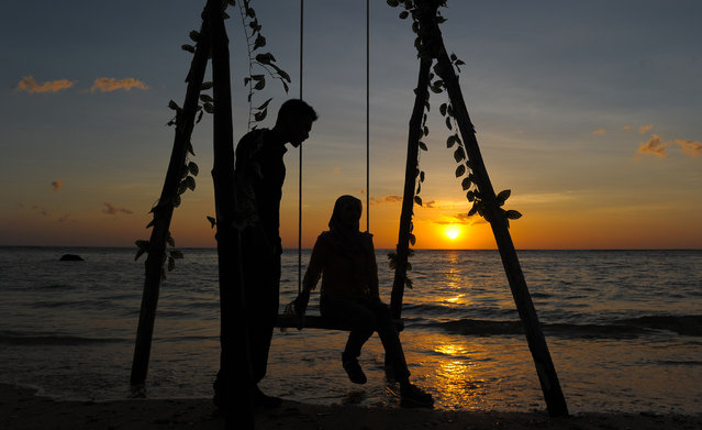 An Acehnese couple enjoy the sunset at Lhok Nga beach during Valentine's day in Aceh, Indonesia on February 14, 2017. (Photo by Chaideer Mahyuddin/AFP Photo)