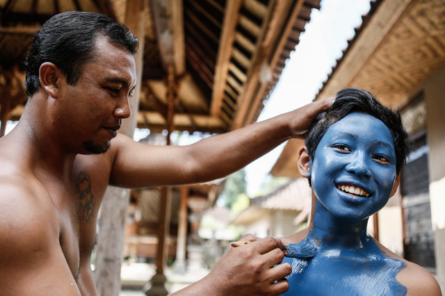 A man paints a boy's body in preparation for the Grebeg ritual on June 25, 2014 in Tegallalang Village, Gianyar, Bali, Indonesia. During the biannual ritual, young members of the community parade through the village with painted faces and bodies to ward off evil spirits. (Photo by Putu Sayoga/Getty Images)