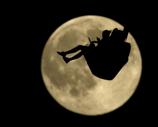 A girl is silhouetted against a rising full moon as she ride an attraction at Worlds of Fun amusement park Thursday, July 30, 2015, in Kansas City, Mo. (Photo by Charlie Riedel/AP Photo)