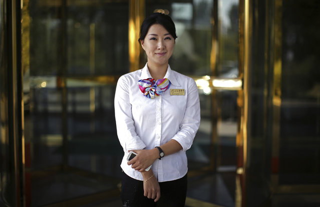 """In this October 14, 2015, photo, Kil Jin A, 29, poses for a portrait at the entrance of the Pothonggang Hotel where she works with mobile phone service provider Koryolink, in Pyongyang, North Korea. She has been working with Koryolink for 8 years and enjoys her job as a sales executive because it gives her opportunities to meet visitors from abroad. Her motto: """"To always help others, but of course, patriotism towards my country is most important"""". (Photo by Wong Maye-E/AP Photo)"""