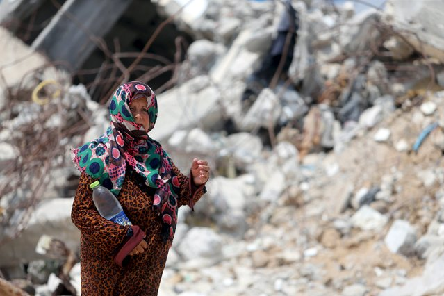A Palestinian woman, whose house was destroyed by what witnesses said was Israeli shelling during a 50-day war last summer, holds a bottle as she walks outside her makeshift shelter during a wave of heat in Khan Younis in the southern Gaza Strip August 3, 2015. (Photo by Ibraheem Abu Mustafa/Reuters)