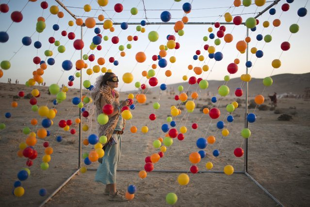 A picture made available on 11 June 2016 shows a festival goer standing inside an art installation during the Israel Midburn festival in the Negev desert southern Israel, 09 June 2016. About 8,000 people attended the colorful festival which is the Israeli version of the well known Burning man festival in Nevada, USA. (Photo by Abir Sultan/EPA)
