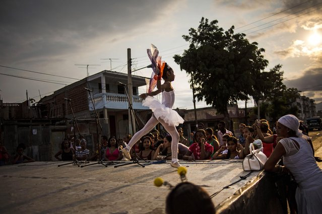 In this March 21, 2015 photo, a ballerina performs at a youth fair in her neighborhood in Santiago, Cuba. The contrast between hope and desperation is starker in eastern Cuba, which is a poorer area, isolated from the capital where detente with the United States has unleashed giddy waves of optimism. (Photo by Ramon Espinosa/AP Photo)