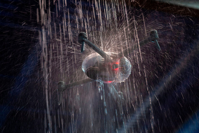 The PowerEgg X autonomous personal AI camera converts into a drone and flies through falling water at the 2020 Consumer Electronics Show (CES) in Las Vegas, Nevada on January 9, 2020. (Photo by David McNew/AFP Photo)