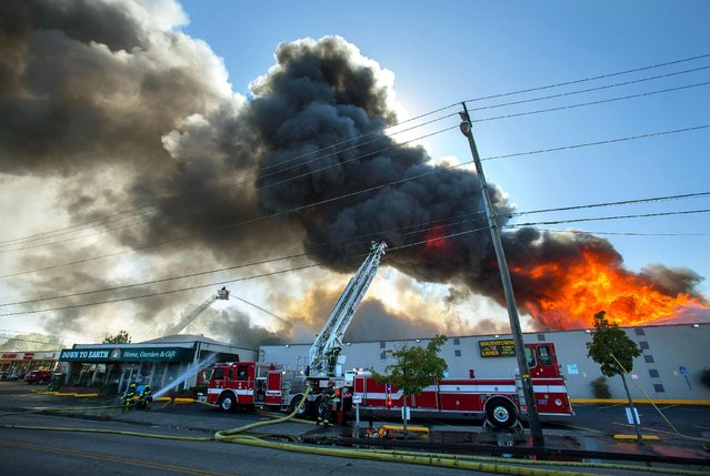 Firefighters fight a two-alarm fire at Southtowne Lanes in Eugene, Ore. Wednesday, August 5, 2015. Fire Marshal Al Gerard said at the scene that firefighters first responded at 3:55 p.m. and went inside the bowling alley. But they were quickly overwhelmed by smoke and flames, and had to retreat and fight the fire from outside. (Photo by Brian Davies/The Register-Guard via AP Photo)