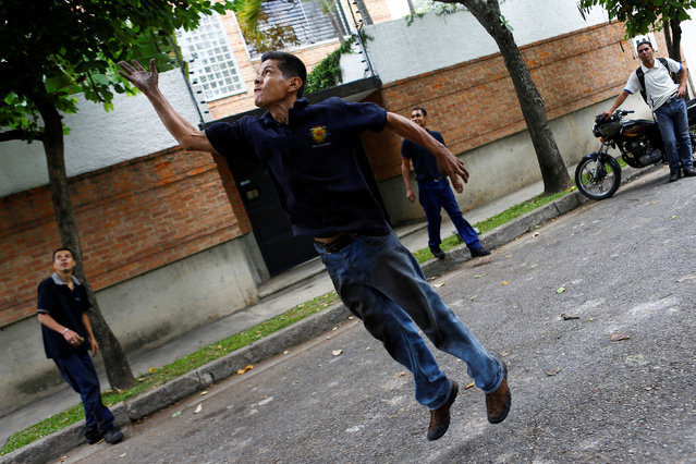 A worker jumps as he throw an object towards a mango tree to try to dislodge the fruits during their lunch break in Caracas, Venezuela, June 17, 2016. (Photo by Ivan Alvarado/Reuters)