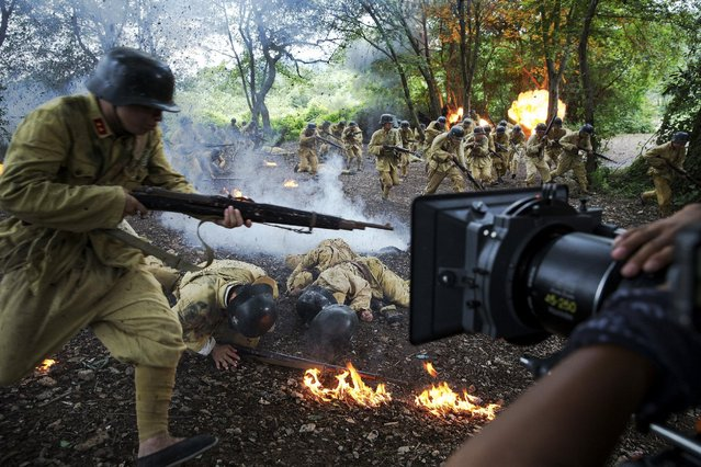 """The camera rolls as actors dressed as historical Chinese soldiers act as though they have been hit by artillery fire, during filming of """"The Last Prince"""" television series on location near Hengdian World Studios near Hengdian July 24, 2015. (Photo by Damir Sagolj/Reuters)"""