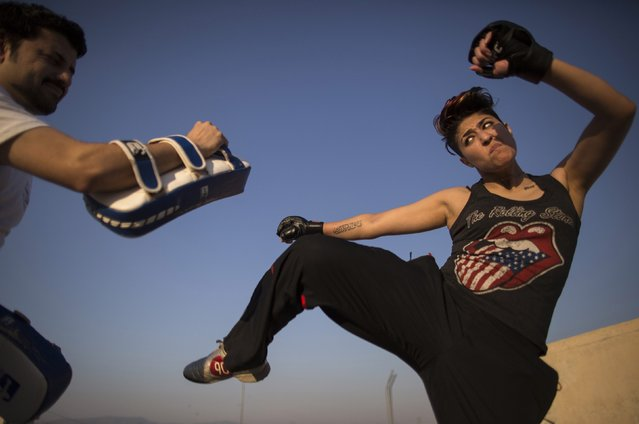 Interior designer Zahra Afridi (R) kicks a punching bag during a kickboxing training session at her home in Islamabad February 10, 2014. Afridi runs her own interior design company. Her most recent project was a Classic Rock Coffee cafe in Islamabad. (Photo by Zohra Bensemra/Reuters)