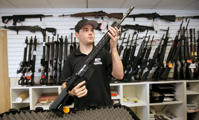 """Salesman, Ryan Martinez inspects a new AR-10 at the """"Ready Gunner"""" gun store in Provo, Utah, U.S., June 21, 2016. (Photo by George Frey/Reuters)"""