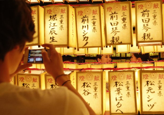 A man takes pictures of women behind paper lanterns during the annual Mitama Festival at the Yasukuni Shrine in Tokyo July 13, 2014. Over 30,000 lanterns light up the precincts of the shrine, where more than 2.4 million war dead are enshrined, during the four-day festival. The festival goes on till July 16. (Photo by Yuya Shino/Reuters)
