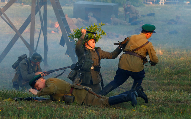 Military enthusiasts dressed as Nazi troops and Soviet Red Army take part in a re-enactment of a World War II battle at the Hero fortress as they mark the 75th anniversary of the Nazi Germany invasion, in Brest, Belarus June 22, 2016. (Photo by Vasily Fedosenko/Reuters)