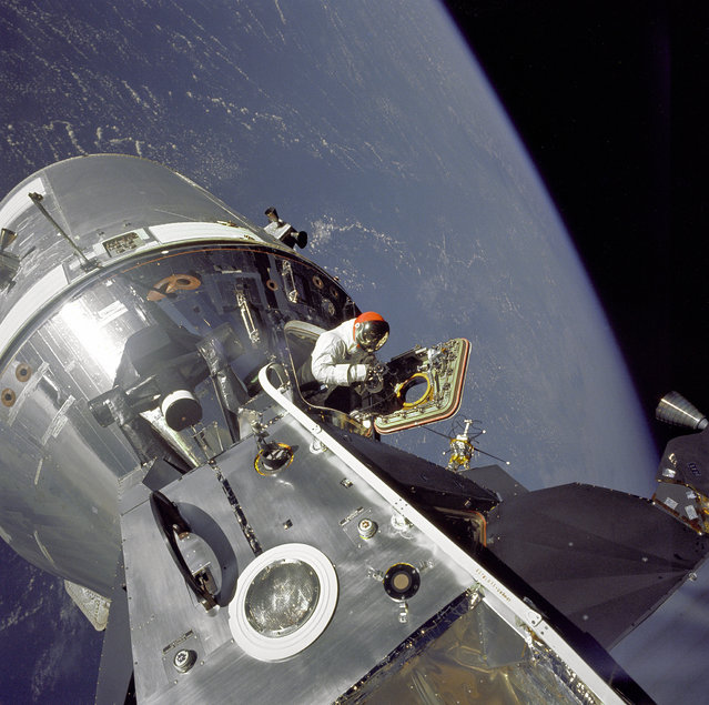 "Apollo 9 Command/Service Modules (CSM) nicknamed ""Gumdrop"" and Lunar Module (LM), nicknamed ""Spider"" are shown docked together as Command Module pilot David R. Scott stands in the open hatch. Astronaut Russell L. Schweickart, Lunar Module pilot, took this photograph of Scott during his EVA as he stood on the porch outside the Lunar Module. Apollo 9 was an Earth orbital mission designed to test docking procedures between the CSM and LM as well as test fly the Lunar Module in the relative safe confines of Earth orbit. (Photo by NASA)"