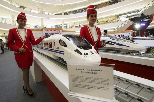 Attendants pose for a photo beside the models of a high speed train during the China High Speed Railway on Fast Track exhibition in Jakarta, Indonesia, August 13, 2015 in this photo taken by Antara Foto.   China has sweetened its bid in a race with Japan to win the construction contract for a high-speed railway connecting Jakarta to the city of Bandung, Indonesia said on Tuesday. (Photo by Rivan Awal Lingga/Reuters/Antara Foto)